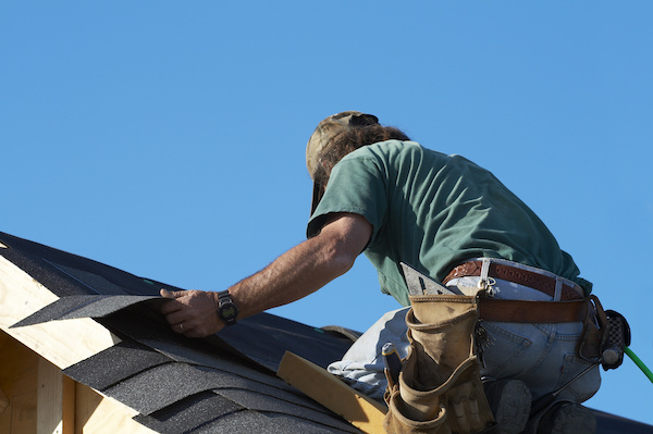 Man replacing shingle on leaky roof
