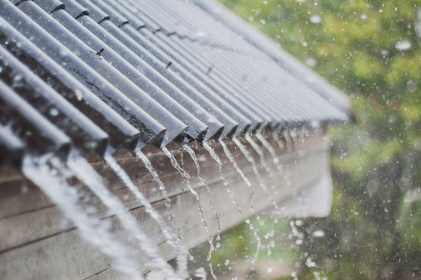 water flowing off of roof during rain storm
