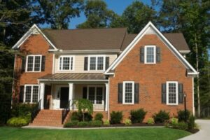 a traditional brick house with a peaked roof to showcase why homeowners need to call a frederick roofing company