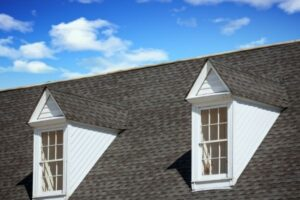 a peaked roof with shingles and two windows set against a blue sky to represent the need to call roofers in maryland for roof repairs