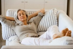 Why replacing your residential roof is a good idea: better energy efficiency for a cooler home. shown here is an elderly woman with grey hair relaxing indoors on a sofa with a striped pillow to represent relaxation