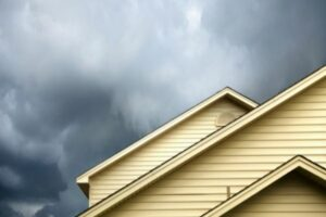 a new roof installation in maryland protects homes against bad weather. this photo depicts a yellow house with storm clouds rolling in.