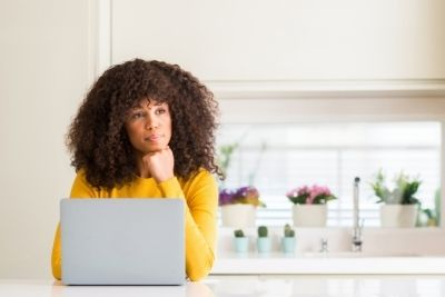 woman in yellow looking perplexed over a laptop as she ponders what questions to ask her roofing contractors